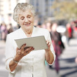 portrait of senior woman touching digital tablet at city