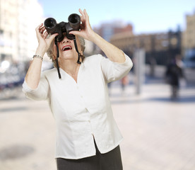 portrait of senior woman looking through a binoculars at city