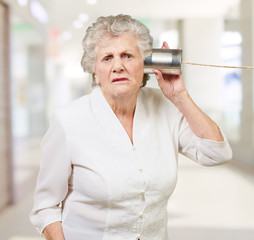 Portrait of a senior woman hearing with metal tin