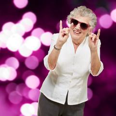 portrait of a happy senior woman doing rock symbol against a abs