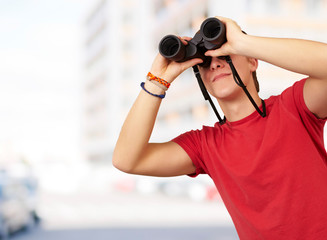 portrait of young man with binoculars against a building