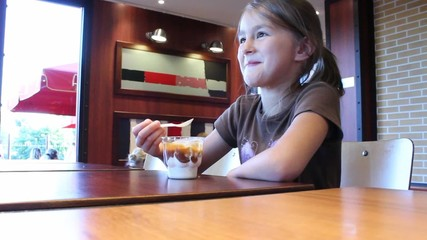 Little girl  eating  bowl of ice cream.