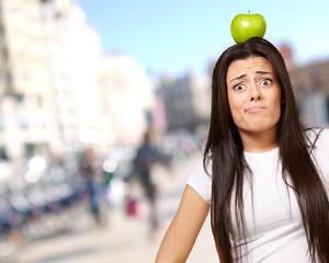 portrait of young woman holding green apple on her head at crowd