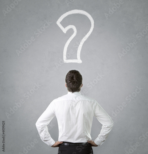 Confused, young businessman looking at question mark