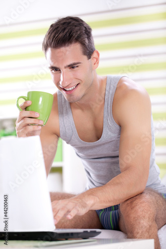 Young men in pajama using laptop