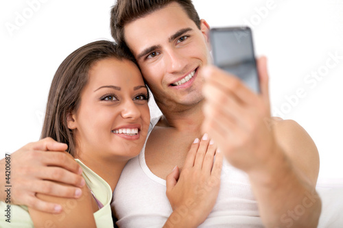 Affectionate couple take photo by mobile phone