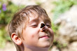 Young boy smiling with butterfly on his nose in summer