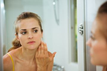 Young woman checking her face in mirror in bathroom