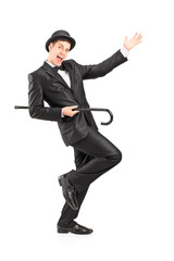 Full length portrait of a performer dancing with a cane