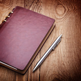 notebook and pen on wood background