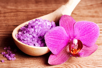 bath salt in a spoon and flowers of orchids