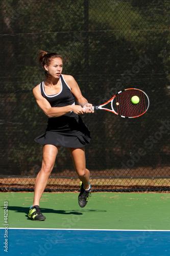 Female Tennis Player Hits Backhand