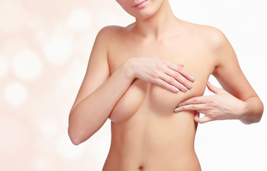 Woman pressing her breast to check the breast cancer