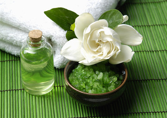 gardenia flower with towel with essential oil on green mat