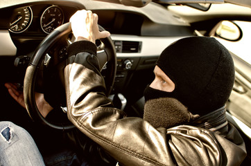 Bandit in mask stealing a car. Close up