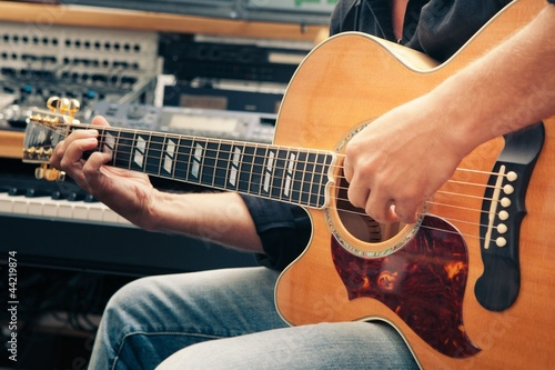 left-handed man playing guitar, close-up
