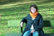 Woman sitting in autumnal park on the park bench