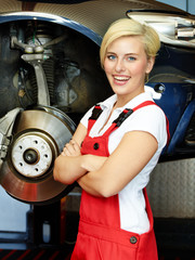 Female apprentice in a garage learning to fix a brake