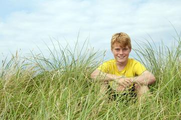 Junge im Dünengras
