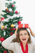 Happy young woman holding Christmas present box on head