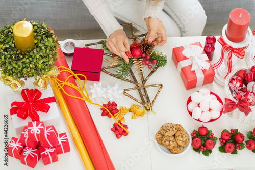 Closeup on table where woman making Christmas decorations. Upper