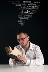 Young man reading a book against black background with text