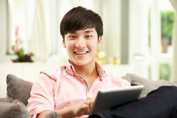 Young Chinese Man Using Digital Tablet Whilst Relaxing On Sofa