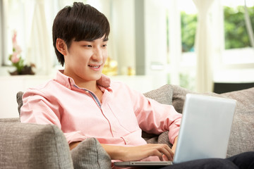 Young Chinese Man Using Laptop Whilst Relaxing On Sofa At Home
