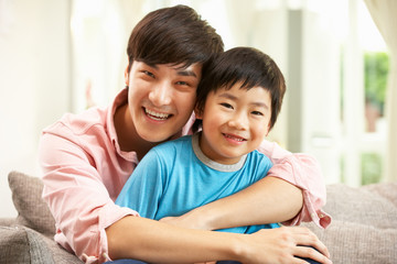 Chinese Father And Son Relaxing On Sofa At Home