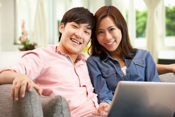 Young Chinese Couple With Laptop Whilst Relaxing On Sofa At Home