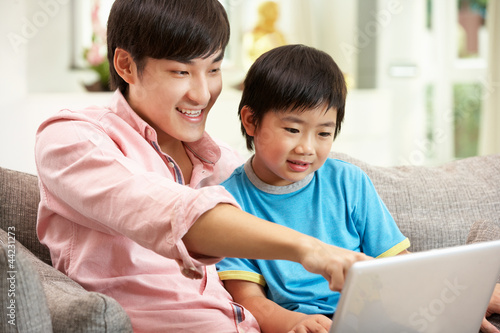 Chinese Father And Son Using Laptop Whilst Relaxing On Sofa