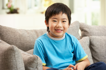 Young Chinese Boy Sitting On Sofa At Home