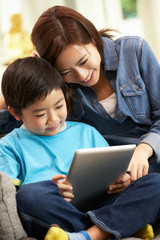Chinese Mother And Son Using Tablet Computer Whilst Sitting On S