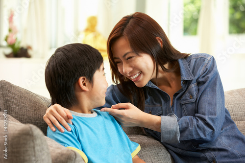 Chinese Mother And Son Sitting On Sofa At Home Together