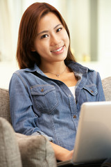 Young Chinese Woman Using Laptop Whilst Relaxing On Sofa At Home