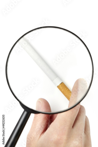 Hand taking cigarette viewed through magnifying glass