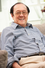 Senior Chinese Man Relaxing On Sofa At Home