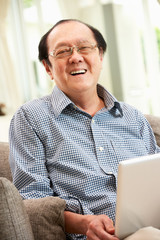 Senior Chinese Man Using Laptop Whilst Relaxing On Sofa At Home