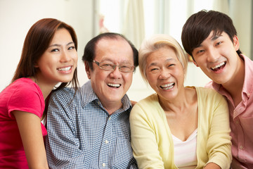 Portrait Of Chinese Parents With Adult Children Relaxing At Home