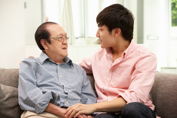 Portrait Of Chinese Father With Adult Son Relaxing At Home