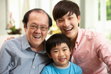 Male Multi Generation Chinese Family Group Relaxing At Home
