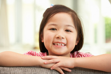Young Chinese Girl Relaxing On Sofa At Home