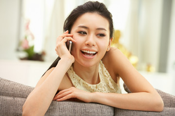 Young Chinese Woman Using Mobile Phone On Sofa At Home