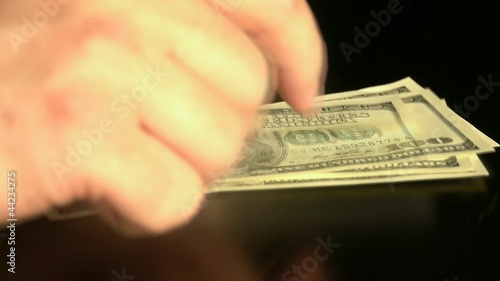 100 Dollar banknote on the table.Hand. Hard shadow.