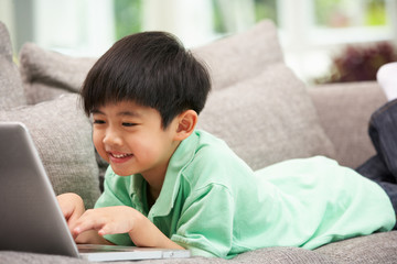 Young Chinese Boy Using Laptop Whilst Relaxing On Sofa At Home