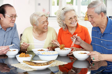 Group Of Senior Chinese Friends Eating Meal At Home