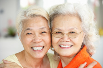 Portrait Of Two Senior Chinese Women Sitting At Home