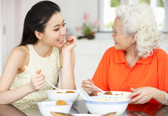 Chinese Mother And Adult Daughter Eating Meal Together