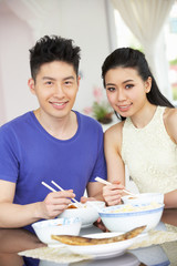 Young Chinese Couple Sitting At Home Eating Meal