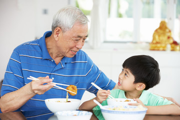 Chinese Grandfather And Grandson Eating Meal Together